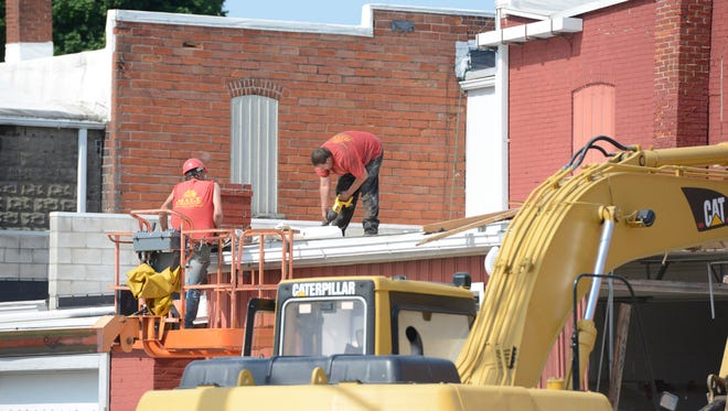 Workers demolish the Lindsey Fire Department building Thursday afternoon.