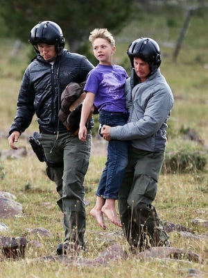 Malachi Bradley is carried from a helicopter before being reunited with his family,  in Uintah County, Utah.