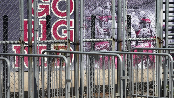 A mural showing Nebraska football players and Go Big Red lettering are seen past locked gates at Memorial Stadium in Lincoln, Neb., Tuesday, Sept. 15, 2020.