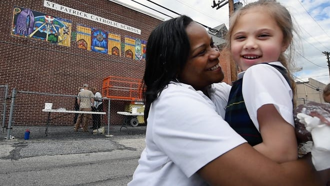 And her outdoor work can be seen in York County. Here, the artist gives kindergarten student Zoe Jones a hug. In the background, Ophelia Chambliss' mural tells a story about community, school and church. The mural on the side of St. Patrick Catholic School was part of the school's 165th anniversary celebration.