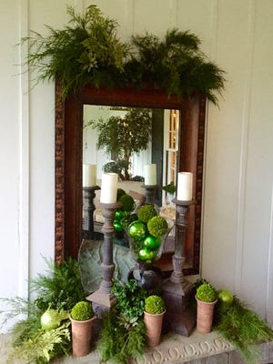 Cedar branches top an antique mirror which reflects the composition of candlesticks and a glass bowl filled with green balls.