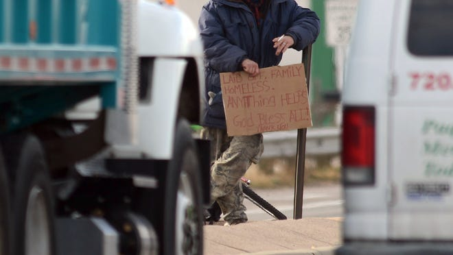 A man panhandles at the intersection of Timberline Road and Mulberry Road Tuesday Dec. 4, 2012.