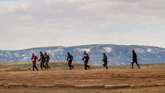 A group of runners participate in the Four Corners Quad Keyah Marathon Series on Thursday at the Four Corners Monument near Teec Nos Pos, Ariz.