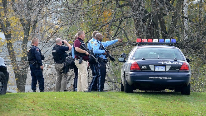 Lansing Police officers are stationed on a hill by Cavanaugh School Thursday as police search for individuals involved in a break-in of a home where gunfire was exchanged. After several hours police had eight people in custody, two who had non-life threatening gunshot injuries. Seven were arrested overnight and one was released.