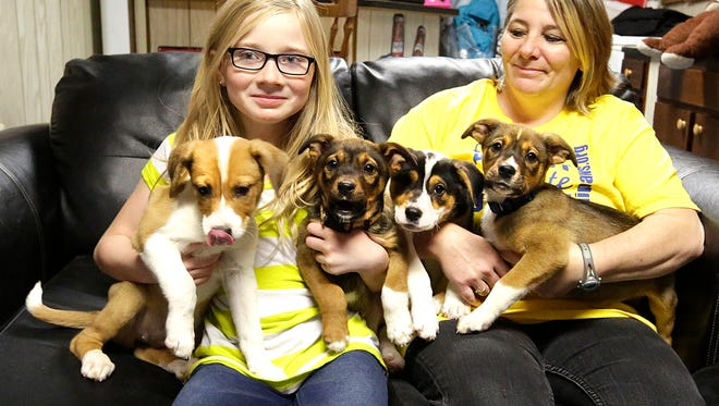 Destonee and Dori Easterson hold four puppies that Dori is fostering for Sandi Paws Rescue.