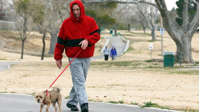 Monday's cold temperatures didn't keep Carlos Lowenberg from walking his dog, Nugget, along the walking trail at Paul Harvey Park in West El Paso Monday. Lowenberg, a long-time area high school football coach, makes the walk with the little pooch a daily routine. A series of weather systems are moving into the El Paso area this week.