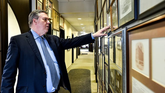 The walls inside Fahey Bank are filled with history of both the bank and the city of Marion. Carl Hughes points out important pieces of the collection of historical documents, photographs and newspaper clippings, some dating to the 19th century.