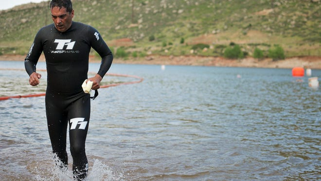 Troy Tafoya, a participant in the Horsetooth Tri Training Series, jogs out of the water Wednesday July 11, 2012 during the transition from the swimming to the running sections.