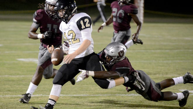 Liberty Tech's Johntazzie Montague chases down a Dyersburg runner as Stephun Bush grabs his legs during their game, Friday. Liberty defeated Dyersburg, 48-19.