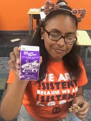 Deborah Cruz, 13, shows off a carton of low-fat milk