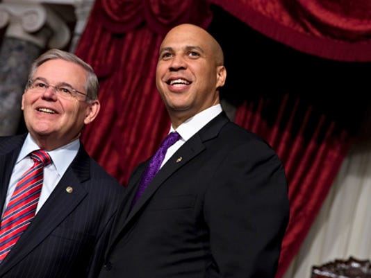 Sen. Cory Booker, right, standing with Sen. Bob Menendez. Booker leads GOP challenger Jeff Bell 43-23, according to a recent poll. (AP photo)