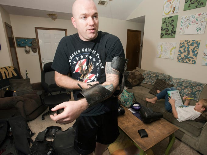 Air Force Staff Sgt. Micah Nelson tries on pieces of