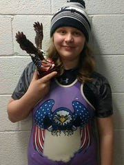 Maddie Rhees, 11, with the runner-up trophy she won at the Ohway Girls State Wrestling Tournament.