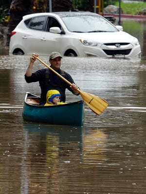 A man paddles a canoe near an abandoned car on a flooded street in Kentfield, Calif.