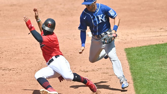 Kansas City Royals second baseman Whit Merrifield, right, chases down Cleveland runner Francisco Lindor (12) in a rundown in the third inning Sunday in Cleveland. The Royals fell to 1-2 with a 9-2 loss.