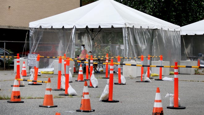 Coronavirus test administrators wait in tents for people to test on Tuesday afternoon at a center set up across from the former St. Joseph Health Center in Providence.