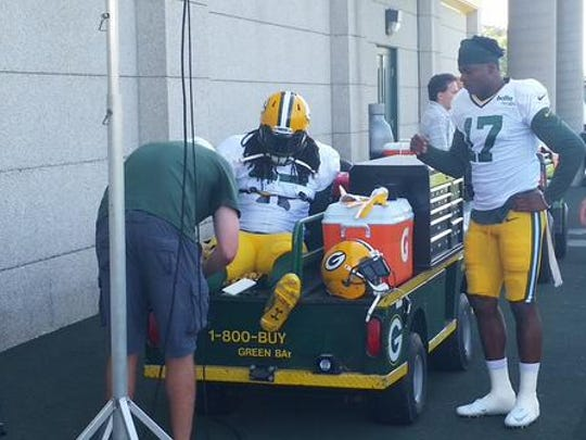 Green Bay Packers running back Eddie Lacy gets treatment on his ankle at the start of practice on Friday. Wide receiver Davante Adams (17) waits in line.