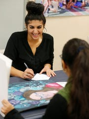 Irvin High School student Kaelyn Monarrez, 17, shows her artwork to Silvia Beatriz Ahisaab, a representative from the Kansas City Art Institute, on Tuesday during the EPISD Fine Arts Departments Visual Arts College Fair. Monarrez was among the students who attended the fair to receive critiques and advice from representatives from art schools who were at the event to recruit students, as well as to provide feedback on how students can improve their work as they follow their dreams of becoming artists.