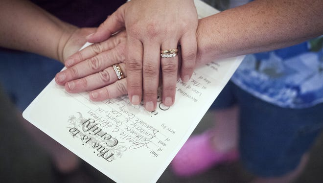 Kimberly Cox and Angelique Hartman sign their wedding certificate following their ceremony at Unitarian Universalist Church in Muncie in 2014.