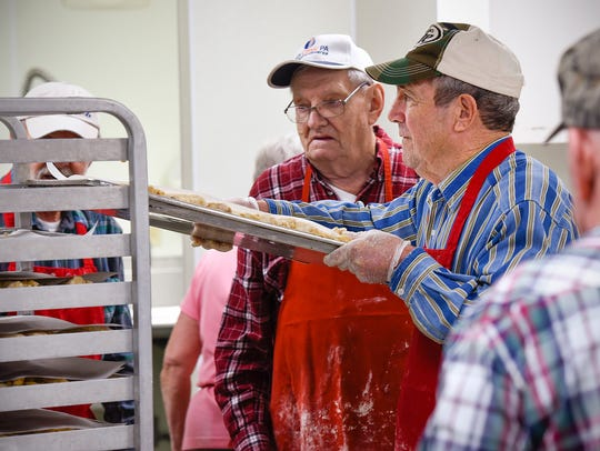 Volunteer Ron Weiman, center, loads a finished pan