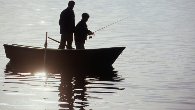 Silhouettes of father and son standing in boat fishing - Generic Image