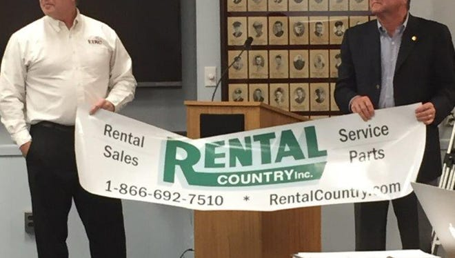 Jack Calkin (left) of EIRC, and Gary Galloway of Rental Country Inc. show the Vineland school board the first ad that will run on 20 district school buses.