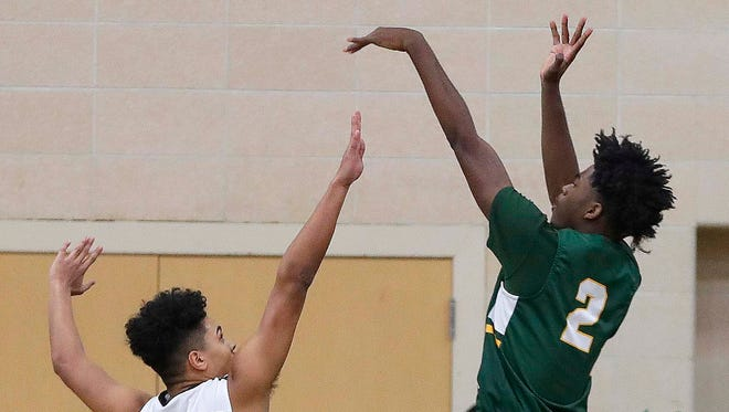 Dominican's Abe Scruggs (left) tries to block a shot by Martin Luther's Ace Evans (2) during the boys basketball game between Dominican and Martin Luther at Dominican in Whitefish Bay, Friday, Jan. 19.