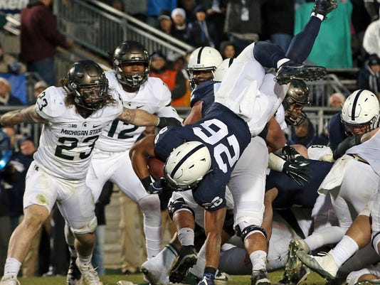 FILE - In this Nov. 26, 2016, file photo, Penn State's Saquon Barkley (26) dives over the pile for a touchdown against Michigan State in the first half of an NCAA college football game in State College, Pa. Barkley struggled against Michigan State last year and this week is coming off a season-low 44-yard game against Ohio State. (AP Photo/Chris Knight, File)