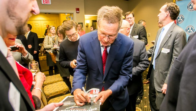 Gov. John Kasich signs a newspaper celebrating Ohio State's recent football national championship before speaking to the South Carolina Republican House Caucus at the Hilton in Columbia, SC, Wednesday evening.