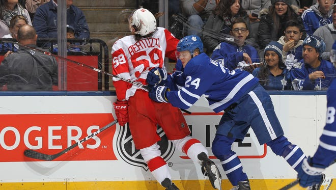 Detroit Red Wings' Tyler Bertuzzi is crushed by Kasperi Kapanen of the Toronto Maple Leafs at the Air Canada Centre on March 24, 2018 in Toronto.