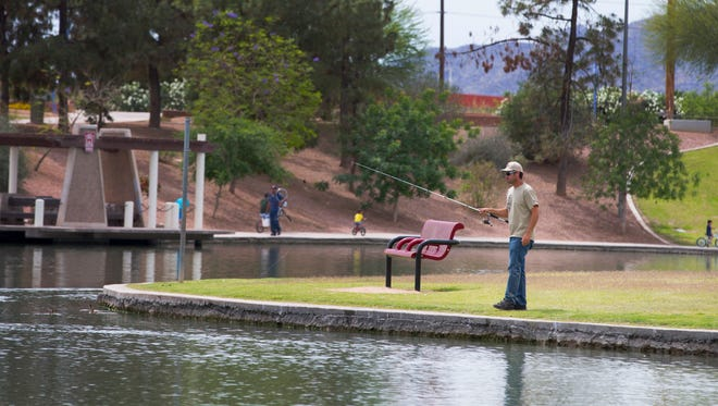 Nathan Foreman, of Queen Creek, fishes at Kiwanis Park in Tempe on April 11, 2015. Gilbert Council member Eddie Cook envisions a comparable regional park of size for the town.