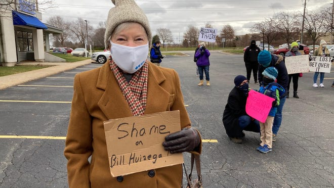 Norma Killilea, of Holland, protests outside U.S. Rep. Bill Huizenga's Grandville office on Sunday, Dec. 13, 2020. Protesters called for Huizenga to resign over his support of Texas v. Pennsylvania, which challenged Michigan's election results.