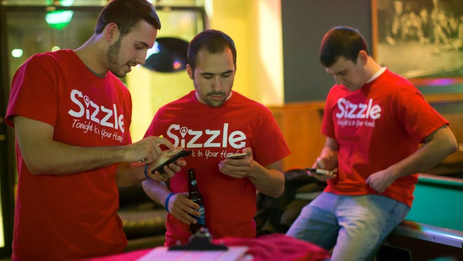"Co-owners Dan Brosman (left) and Max Zirbel look at their Sizzle phone app during an Oshkosh launch March 4. The app won the ""America's Pitch Tank"" competition Thursday night in Appleton."