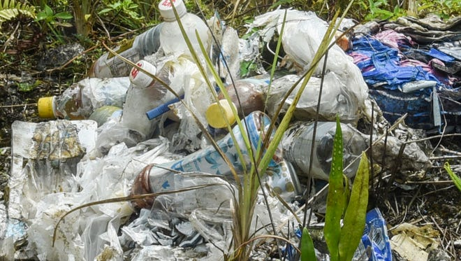 A motorist drives past a collection of trash dumped on the roadside of Chalan Eskuela in Yigo on Wednesday, March 15, 2017.