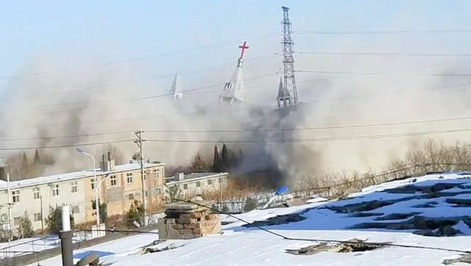 In this image taken from video shot Tuesday, Jan. 9, 2018, by China Aid and provided to the Associated Press, clouds of debris billow during the demolition of the Golden Lampstand Church in Linfen in northern China's Shanxi province. Witnesses and overseas activists say paramilitary troops known as the People's Armed Police used excavators and dynamite on Tuesday to destroy the Golden Lampstand Church, a Christian mega-church that clashed with the government.