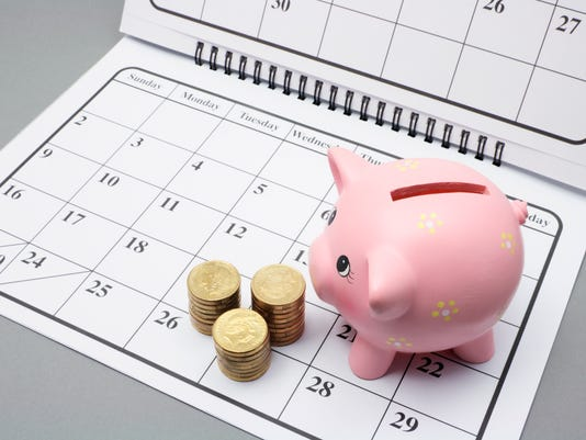 Piggy bank and stack of gold coins on top of a calendar