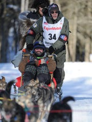 Four-time champion Jeff King mushes through the woods during the ceremonial start of the Iditarod Trail Sled Dog Race in Anchorage, Alaska, Saturday, March 4, 2017.