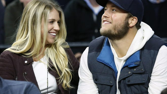 FILE - In this Nov. 17, 2015, file photo, Detroit Lions quarterback Matthew Stafford, right, smiles while watching the Detroit Pistons play the Cleveland Cavaliers with his wife Kelly, left, during the first half of an NBA basketball game, in Auburn Hills, Mich.