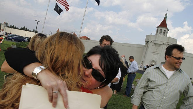 Dee Miller, Batavia, center facing camera, hugs Vickie Menz, West Henrietta, left, following the 40th anniversary memorial ceremony outside Attica prison in Attica Tuesday, Sept. 13, 2011.   Miller is the daughter of guard William Quinn, who was killed by inmates during the riot.  Menz is the daughter of guard Art Smith who was taken hostage during the riot.  The ceremony was put on by the Forgotten Victims of Attica.   (Democrat & Chronicle, Photo by Shawn Dowd, 091311)