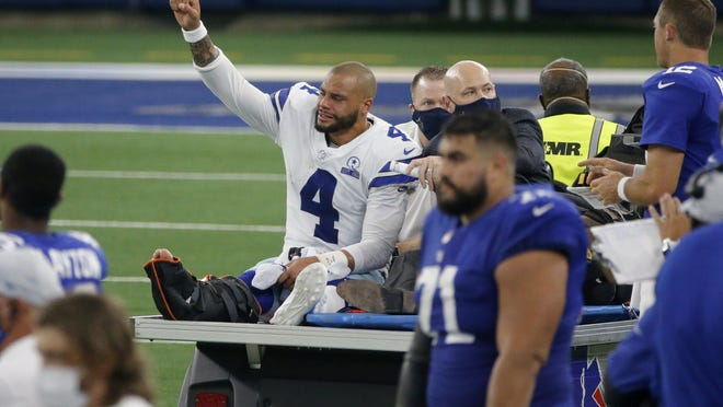 Dallas Cowboys quarterback Dak Prescott (4) lifts his fist to cheers from fans as he is carted off the field after suffering a lower right leg injury running the ball in the second half of an NFL football game against the New York Giants in Arlington, Texas, Sunday, Oct. 11, 2020.