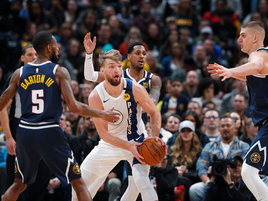 Indiana Pacers forward Domantas Sabonis, center, looks to pass the ball as, from left, Denver Nuggets guards Will Barton and Monte Morris and center Nikola Jokic defend in the second half of an NBA basketball game Sunday, Jan. 19, 2020, in Denver.