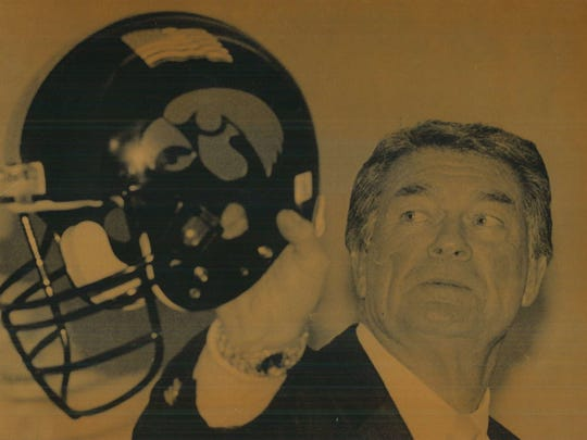Coach Hayden Fry holds an Iowa helmet with an American