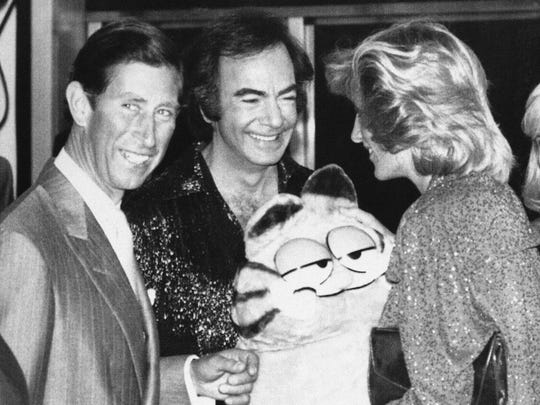 In this 1984 photo, singer Neil Diamond presents a large Garfield plush toy to Princess Diana and Prince Charles.