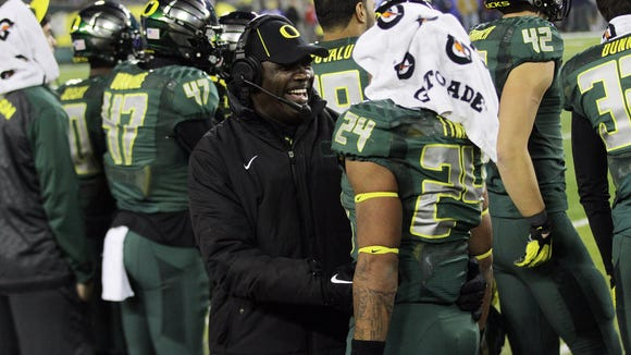 Running backs coach Gary Campbell and Thomas Tyner celebrate as Oregon defeats UCLA 42-14 in a battle of nationally ranked Pac-12 college football teams.