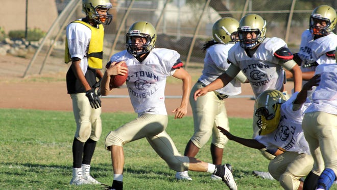 Desert Hot Springs quarterback Andrew Moreno sprints away from defenders during practice on Wednesday, August 12.