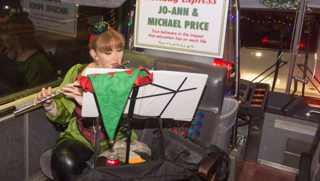 A flautist from Pensacola State College's Performing Arts Department delights guests aboard the bus as they are transported across campus during the 2016 Holiday Experience.