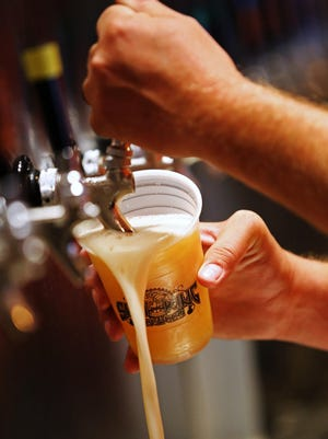 A beer is poured during an opening for family and friends of employees at the new Sun King tap room in Fishers.