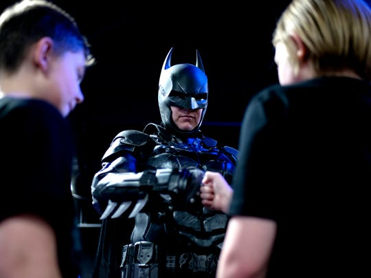 Shamus Smith, dressed as Lansing Batman, center, fist
