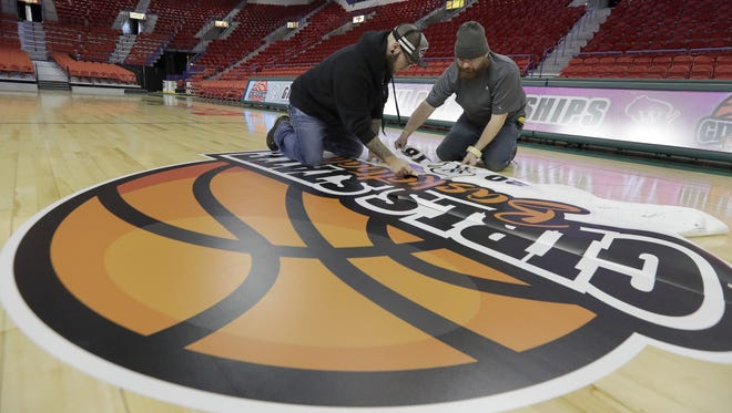 Fast Signs installers Mike Graczyk, right, and Kevin Krebsbach lay down the floor logos for the WIAA state girls basketball tournament Wednesday at the Resch Center in Ashwaubenon.