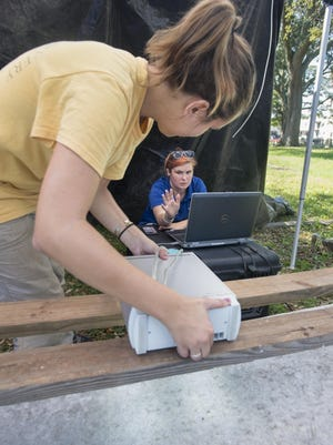 University of West Florida archaeology graduate students Mariana Zechini, left, and Katy Petterson position a NEXT-Engine Desktop 3D scanner over a grave marker in order to help read the worn inscription at St. Michael's Cemetery in Pensacola on Friday, September 23, 2016.